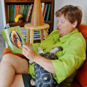 photo of author elaine a powers reading to her tortoise, Myrtle