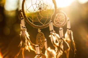 photo of dream catcher with green land and light behind it